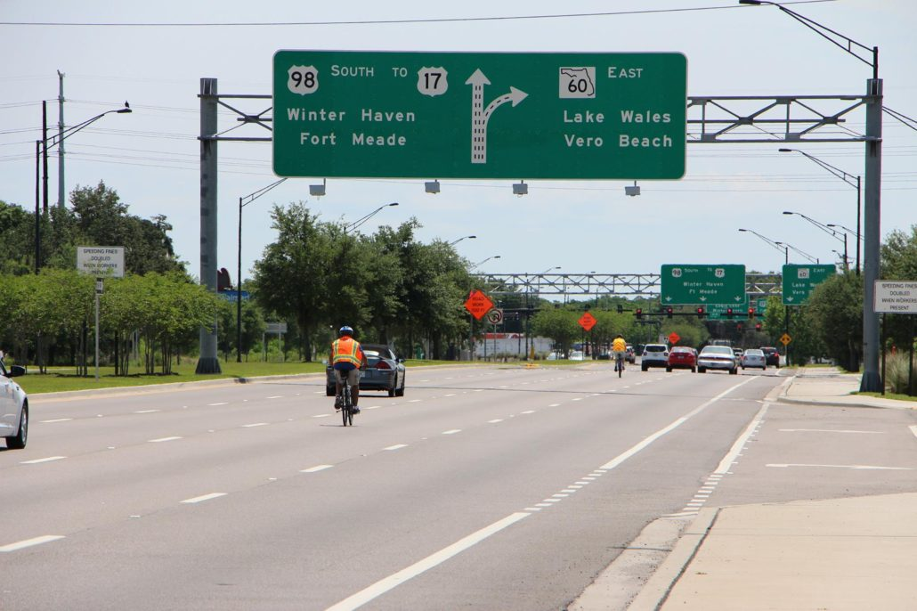 Photo of FDOT staff riding bikes on a busy road in Bartow, FL.