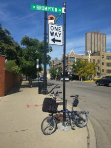 Brompton leaning on street sign pole for W Brompton Avenue in Chicago.