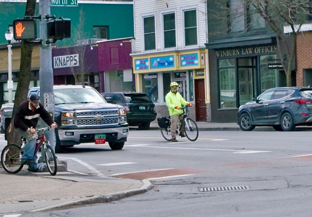 men riding bikes on sidewalk and on road