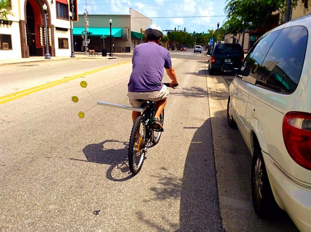 """""""Smiley Faces"""" width extender attached to bicycle"""