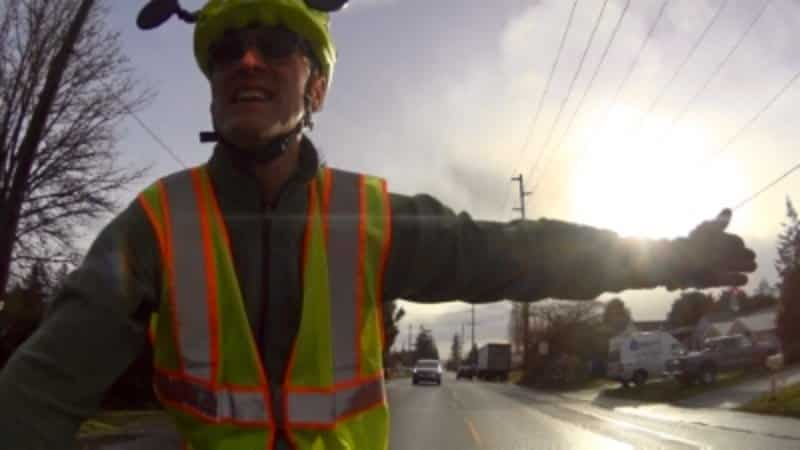Brian signaling a left turn on his bicycle while keeping tabs on traffic behind with his bicycle helmet mirrors