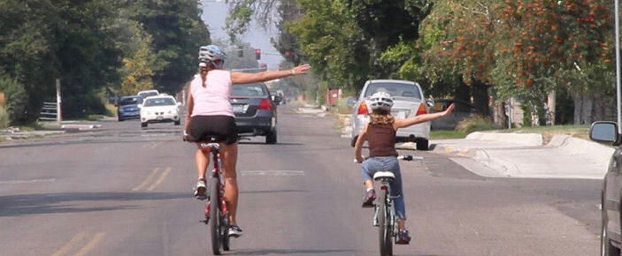 Mother and child riding side by side on a street and both signaling a right turn
