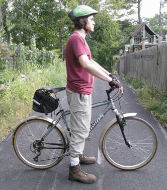 Cyclist standing over a bicycle