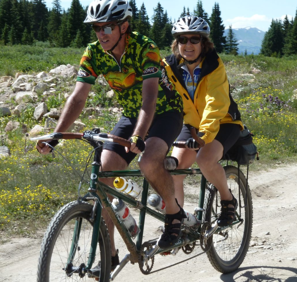 Photo of Mighk & Carol Wilson on their tandem bicycle in the Colorado Rockies.
