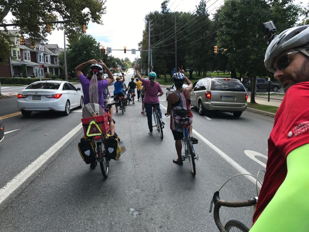 Some are holding up two fingers to let others know that we'll be riding two-by-two to our next stop on this CyclingSavvy road tour.