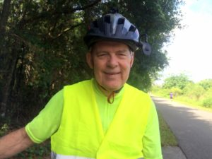 man wearing bike helmet on bike trail