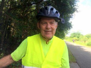 man wearing bike helmet on bike trail
