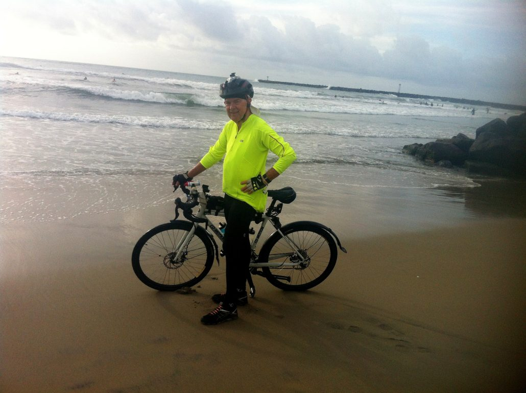 man and touring bike in front of pacific ocean at san diego