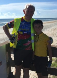 grandpa and grandson with beach behind them