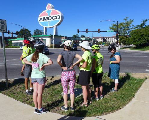 5 women stand next to a man holding a boy on street corner Amoco sign in background
