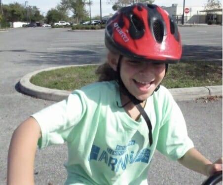 girl on bike with a big smile