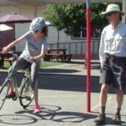 "photo of adult student learning how to ""power pedal"" her bicycle as instructor looks on"
