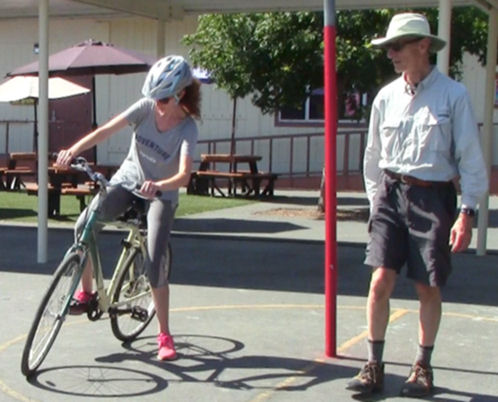 "Adult student learning how to ""power pedal"" her bicycle as instructor looks on"