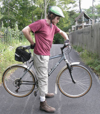 Cyclist lifting a bicycle to check standover clearance